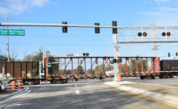 A train passes over Sam Allen Road on January 16 as crews work to prepare the intersection to reopen to traffic