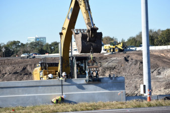 Workers install wall segments along eastbound SR 60 at the entrance ramp to northbound I-75 on January 22, 2020