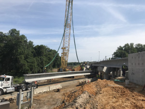 Workers prepare a beam to be lifted into place to widen the ramp bridge over Sligh Avenue. (4/6/19 photo)