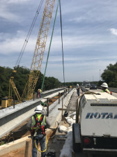 Workers direct a beam into place over Sligh Avenue. This bridge is being widened to create a two lane ramp. (4/6/19 photo)