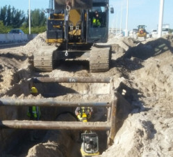 Workers install pipe in a trench box next to I-275