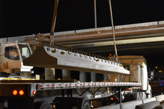 A concrete beam is lifted by crane off a transport truck at SR 60 and I-275 (3/21/2020 photo)