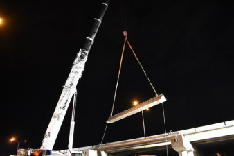 A crane lifts a concrete beam into place at SR 60 and I-275 (3/21/2020 photo)