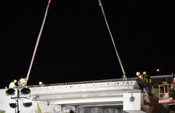 Workers guide a concrete beam into place where the northbound I-275 bridge is being widened over Sr 60 (3/21/2020 photo)