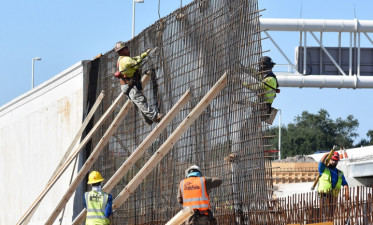 Workers tie steel for noise barrier wall