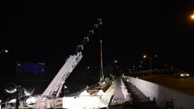 A car on northbound I-275 passes by workers installing bridge beams over SR 60 (3/21/2020 photo)