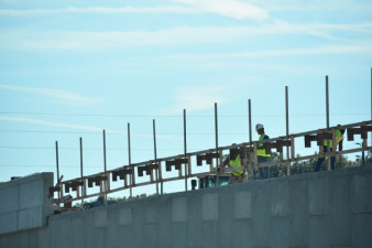 Workers build a wall on the north side of SR 56, east of I-75